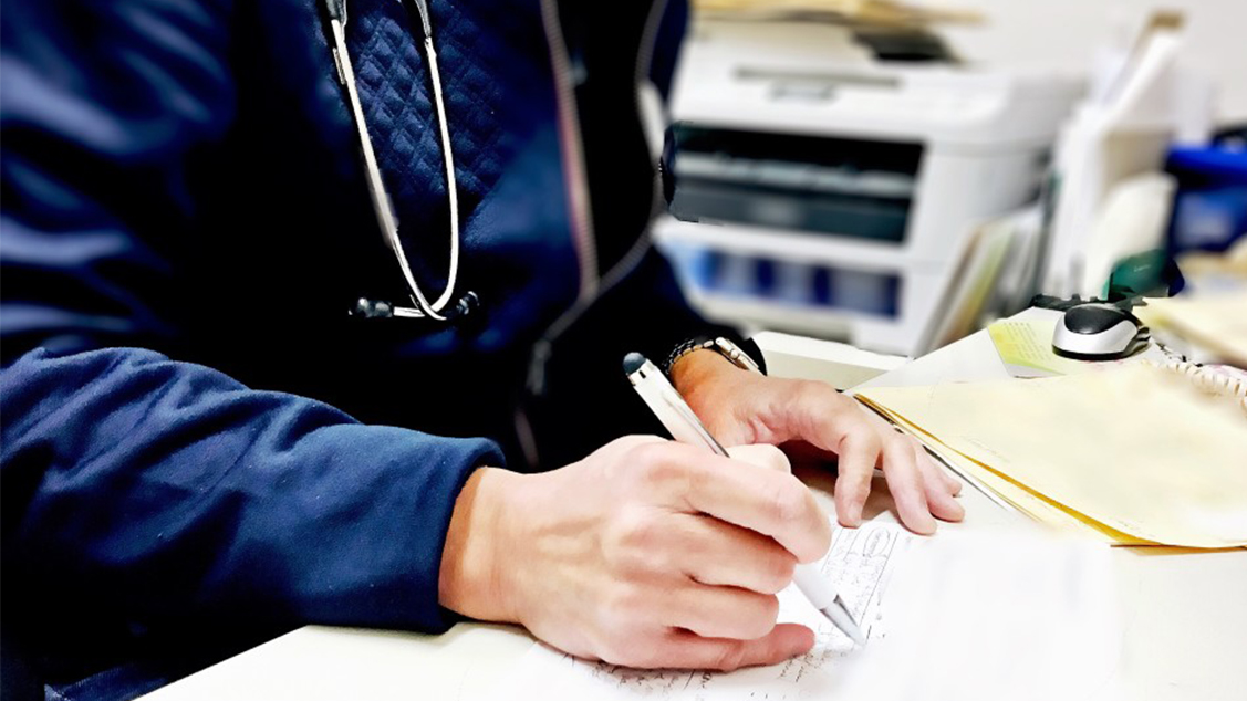 doctor writing on a piece of paper
