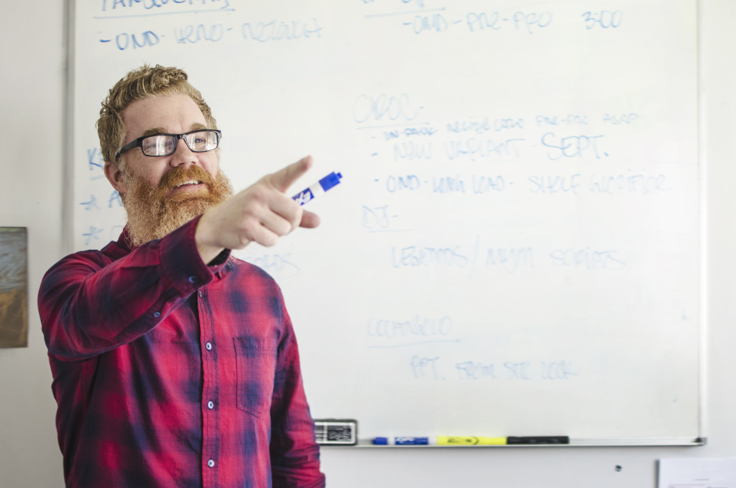 man teaching a class pointing to someone