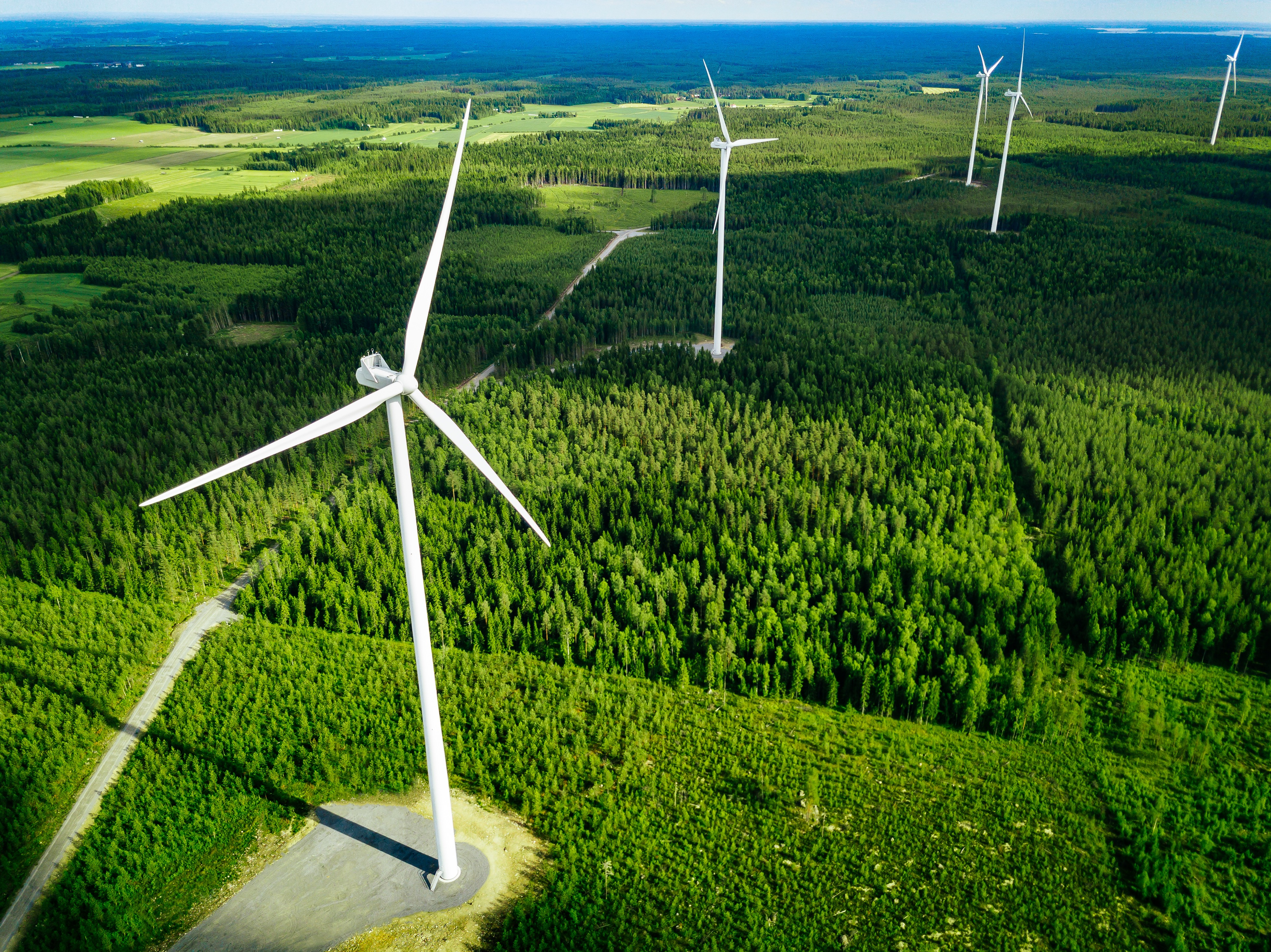 Aerial view of windmills in summer forest in Finland.