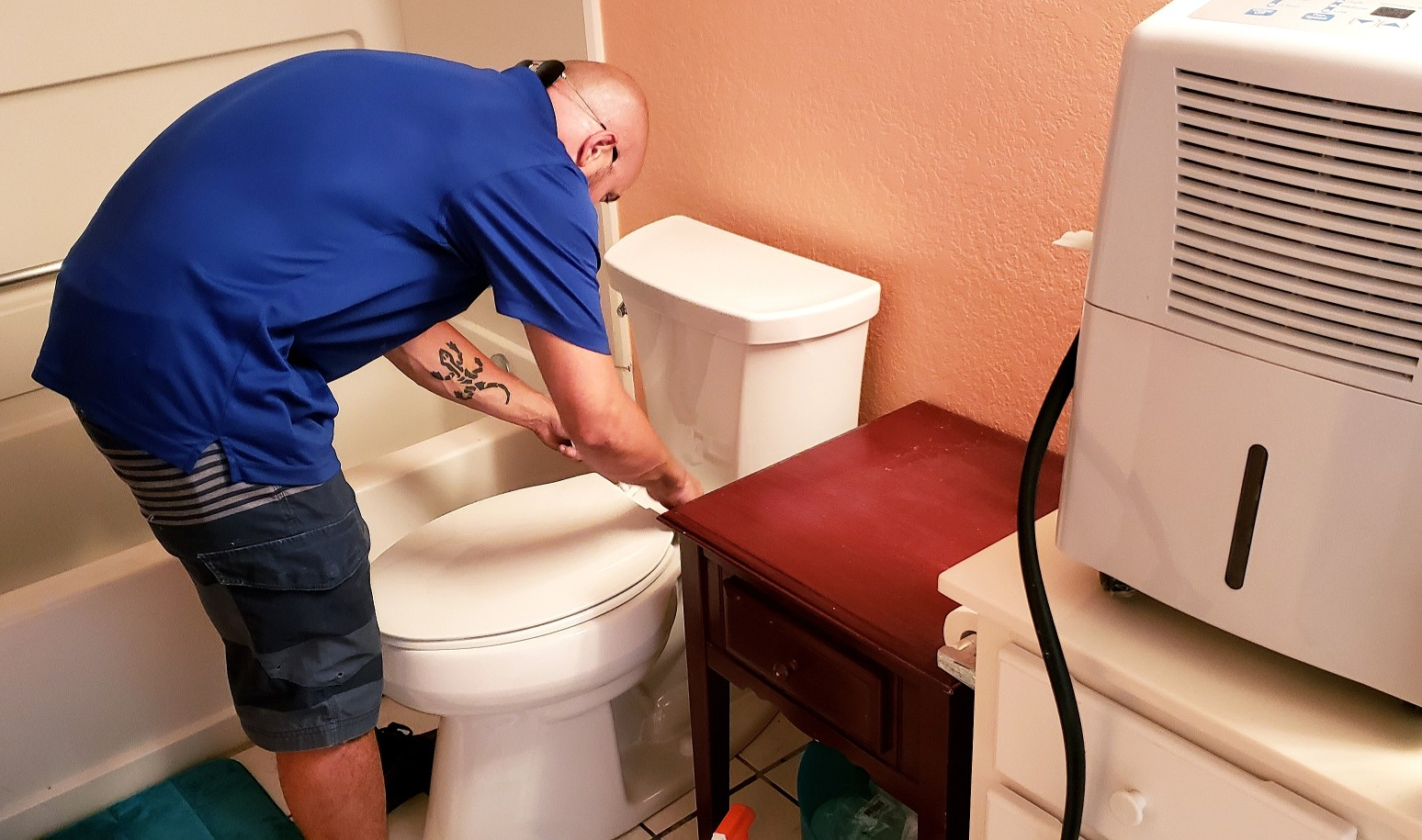 man fixing a toilet