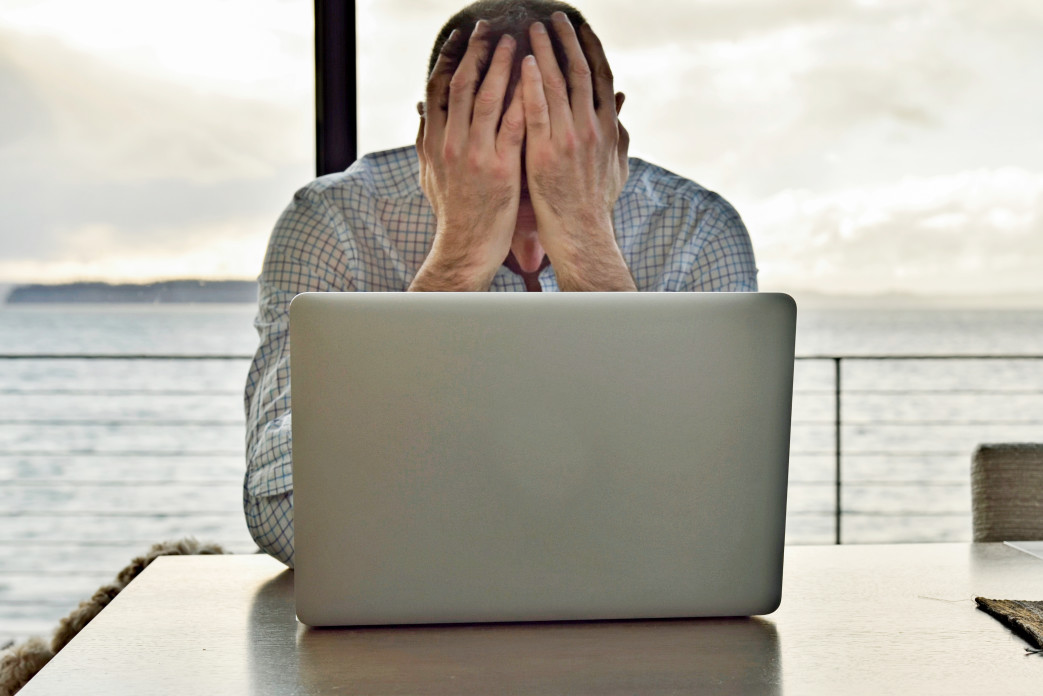 computer-burnout-man-with-hands-covering-face-while-working-with-a-laptop-computer-frustration-stress