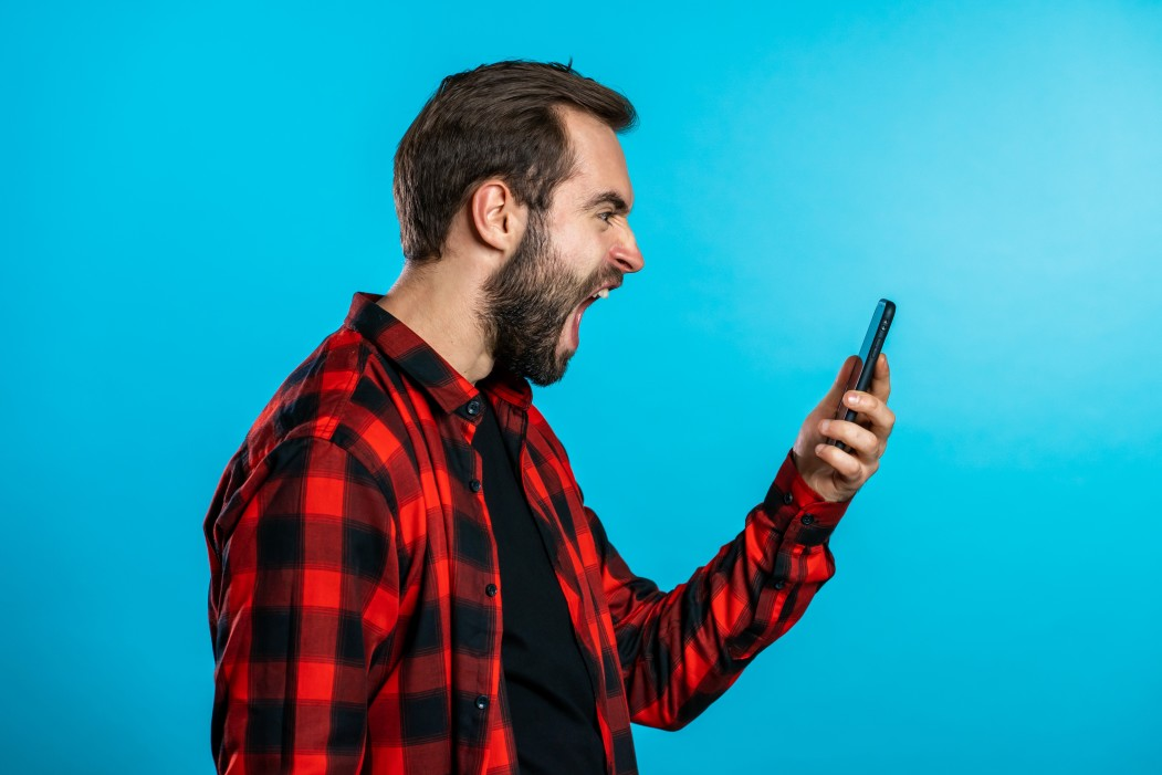 angry-modern-hipster-in-red-plaid-shirt-screaming-down-his-mobile-phone-stressed-and-depressed-man