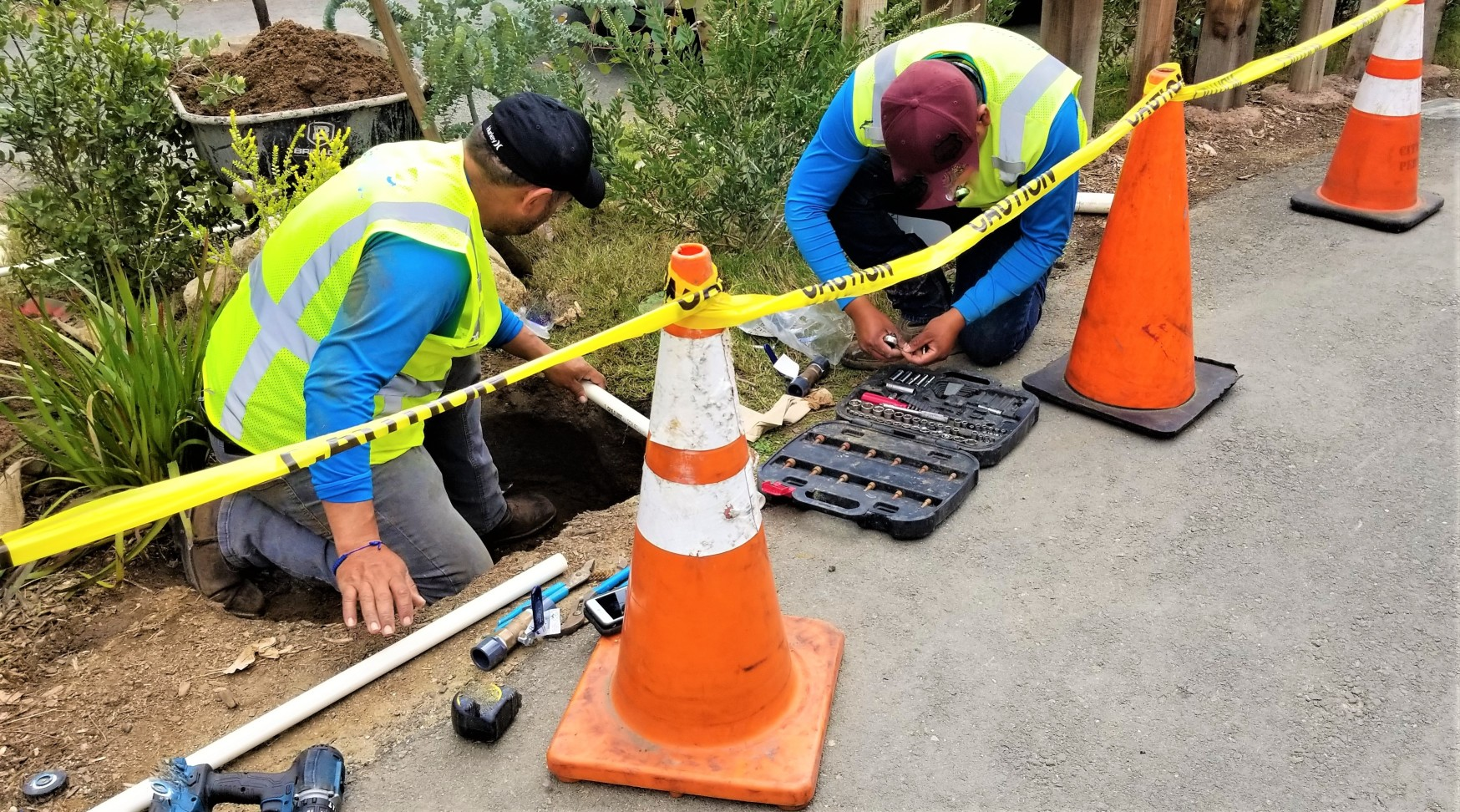 people-two-men-city-workers-in-a-hole-in-the-ground-to-repair-the-plumbing-along-the-sidewalk-in-town